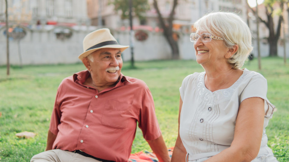 Older couple smiling while sitting on the grass outdoors