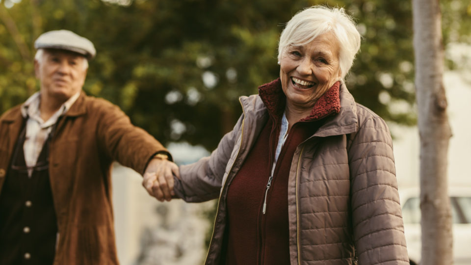 Smiling senior woman holding hand of her partner and walking in front outdoors. Happy senior couple walking outdoors on a winter day.