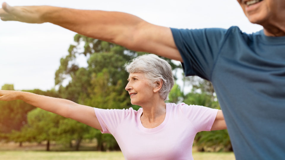 Senior woman stretching arms at park with her husband. Happy aged couple doing yoga exercise outdoor on a bright morning. Smiling elderly woman doing breath exercise with outstretched arms.